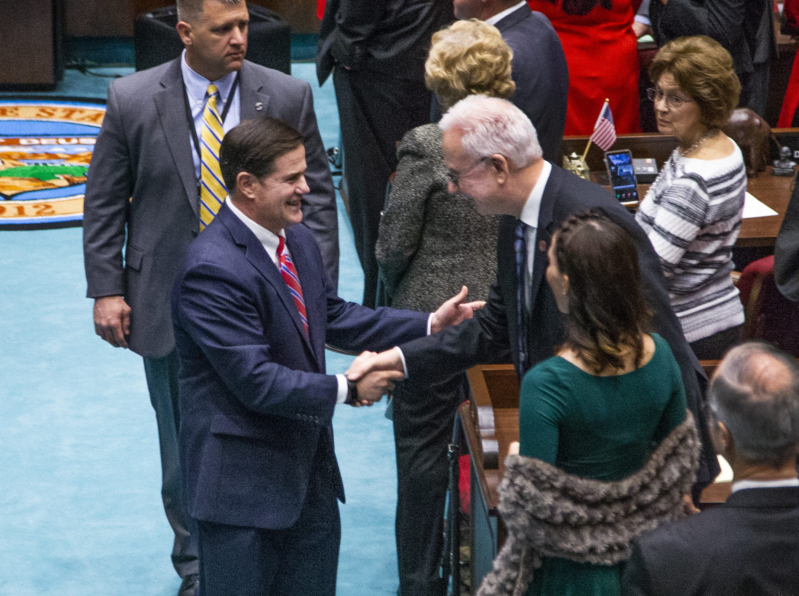 Gov. Doug Ducey greets legislators as he leaves the House of Representatives after delivering his State of the State address to the Legislature and guests gathered at the State Capitol on Jan. 14, 2019.