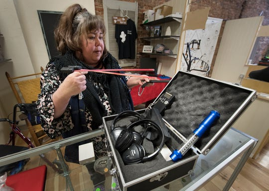 Lora Cole Shirey at her booth with some tools of her trade, dowsing rods, and a photopod inside York Unique Emporium, at 33 W. Market St., where she operates her business York Ghost Tours.