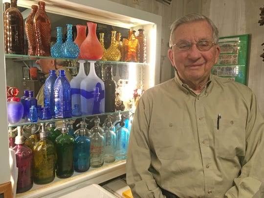 Fred Rosenmiller and a lighted section of his bottle collection.