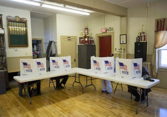Voters fill out ballots at the Becraft volunteer fire company on Tuesday, Nov. 8, 2016, in Greenport, N.Y. (AP Photo/Mike Groll)