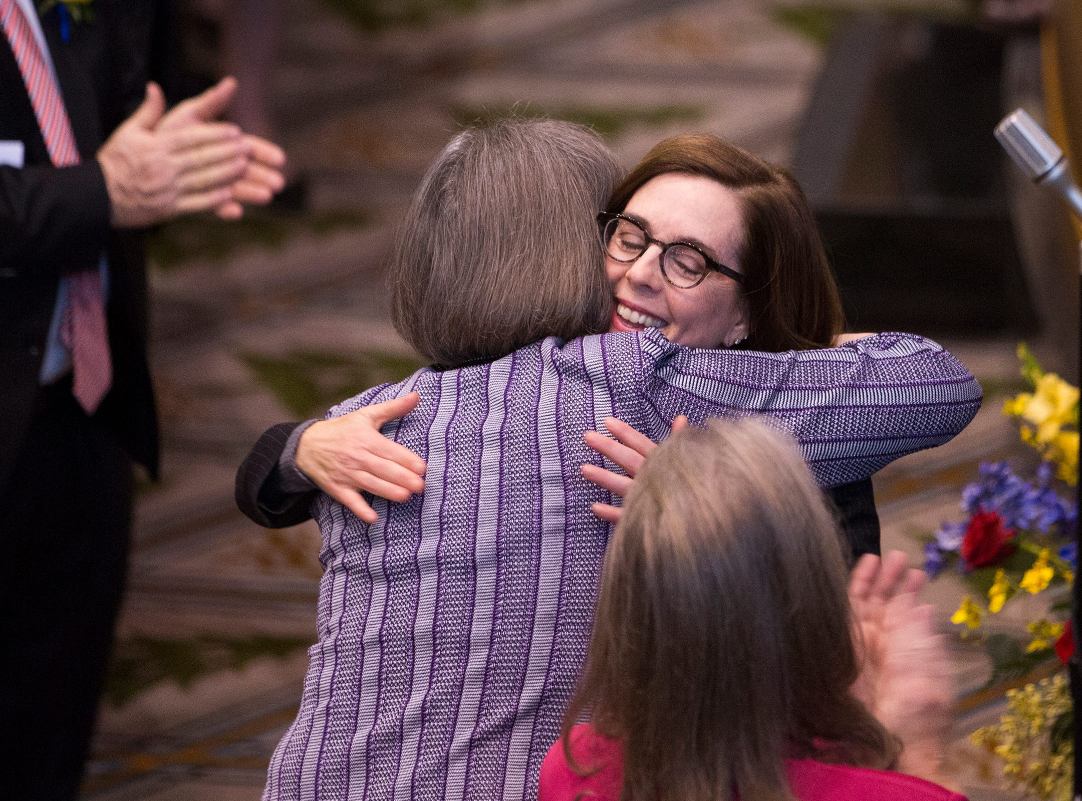 Governor Kate Brown hugs members of the Senate at her inauguration at the Oregon State Capitol on Jan. 14, 2019.