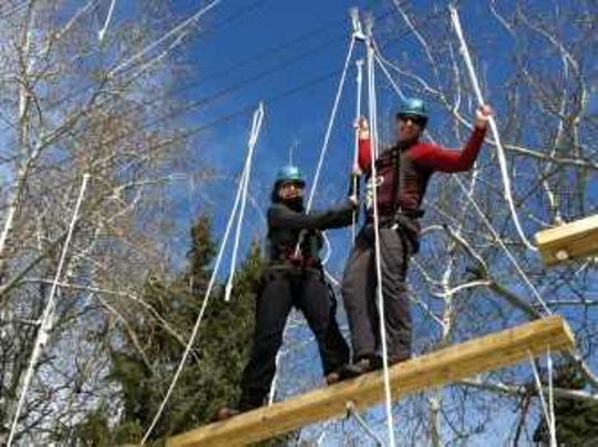 People participating in a ropes course. This type of challenge is coming to Sonrisas Trails in the Summer of 2019.