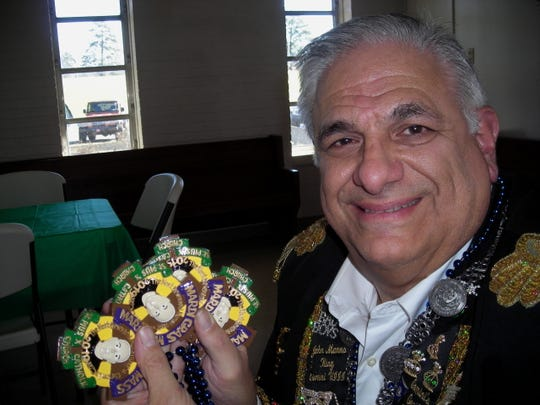 John Manno Jr. holds up bead medallions which honor the late Msgr. Carson Lacaze. They were presented to worshipers arriving  at St. Pius X Catholic Church for Mardi Gras Mass.