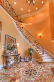The exquisite curved staircase greets guests as they enter the home.