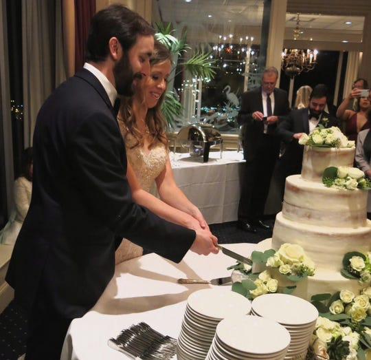William Guston Hall and Kristen Michelle  Rollo cut the bride's cake at their wedding reception at the Petroleum Club.