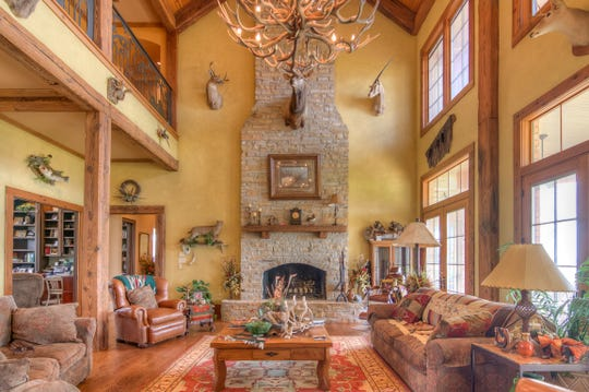 A vast, rustic great room with a wall of windows is lit by an antler chandelier dangling from the 34' vaulted ceilings.