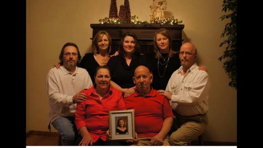 The family of Debbie Martines, who was killed in 1994 by Joaquin Jack Ramos, holds a photo of Debbie. Pictured are her brothers, sisters and parents.