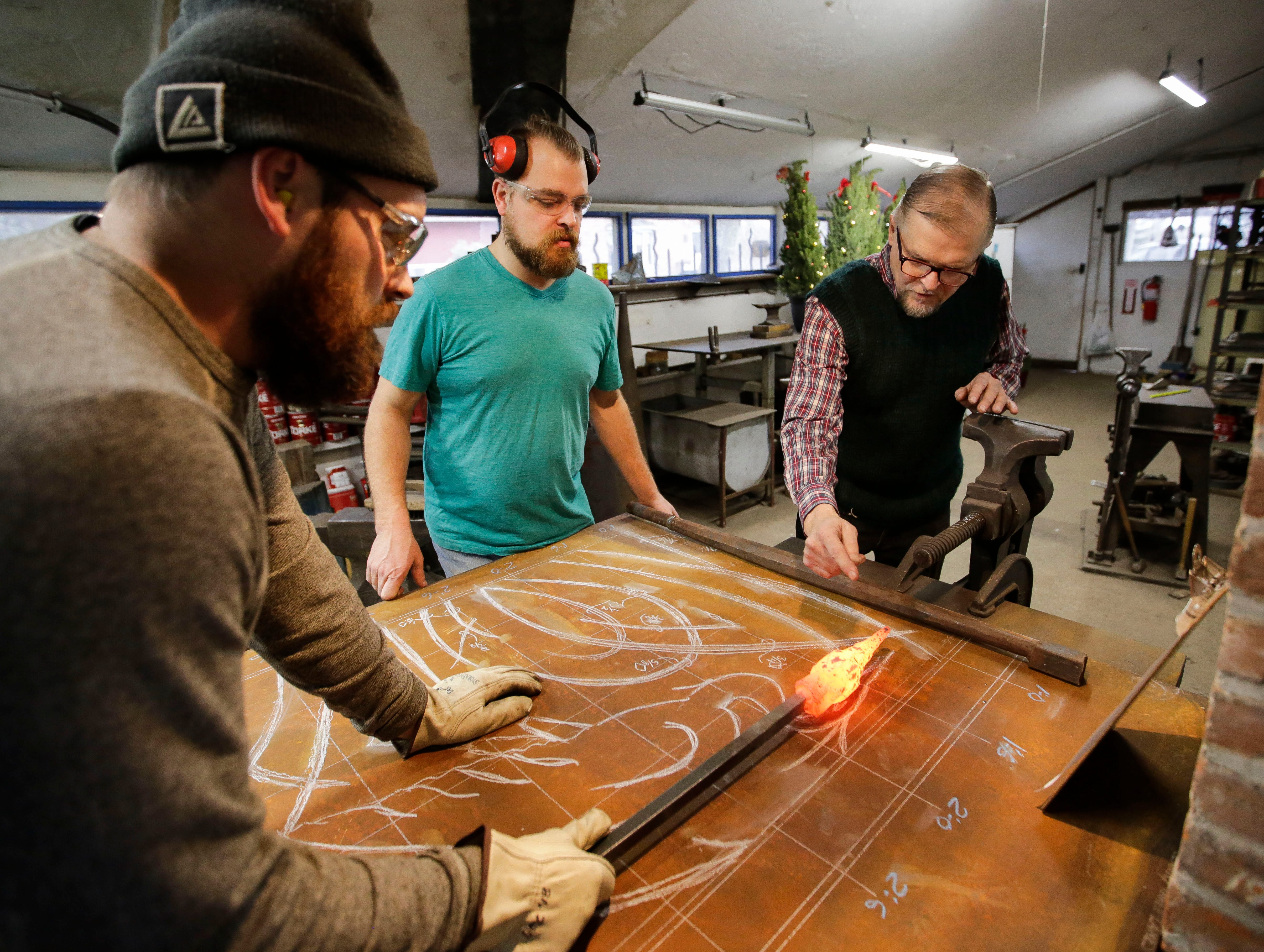 August Kochanowski, Vincent Kochanowski and Boleslaw Kochanowski compare a piece of worked metal to a design sketch on Tuesday, December 25, 2018, at their workshop in Junction City, Wis.