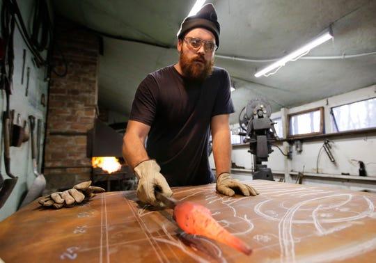 August Kochanowski compares a piece of worked metal to a design sketch on Tuesday, December 25, 2018, at Boleslaw Kochanowski's workshop in Junction City, Wis.Tork Mason/USA TODAY NETWORK-Wisconsin