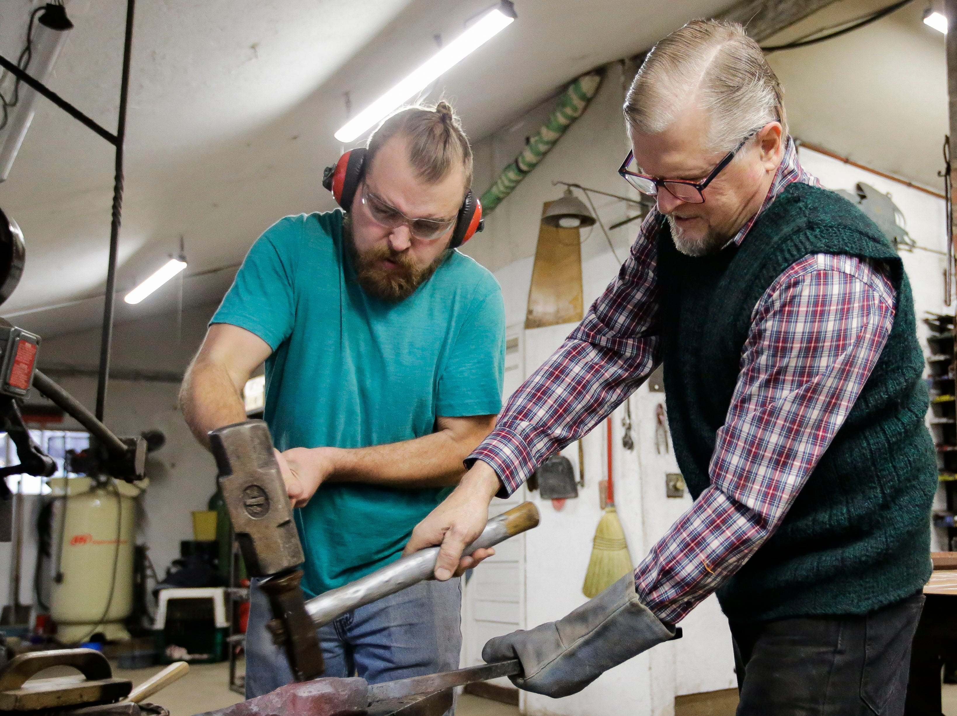 Vincent Kochanowski and Boleslaw Kochanowski hammer out part of a design on Tuesday, December 25, 2018, at their workshop in Junction City, Wis.