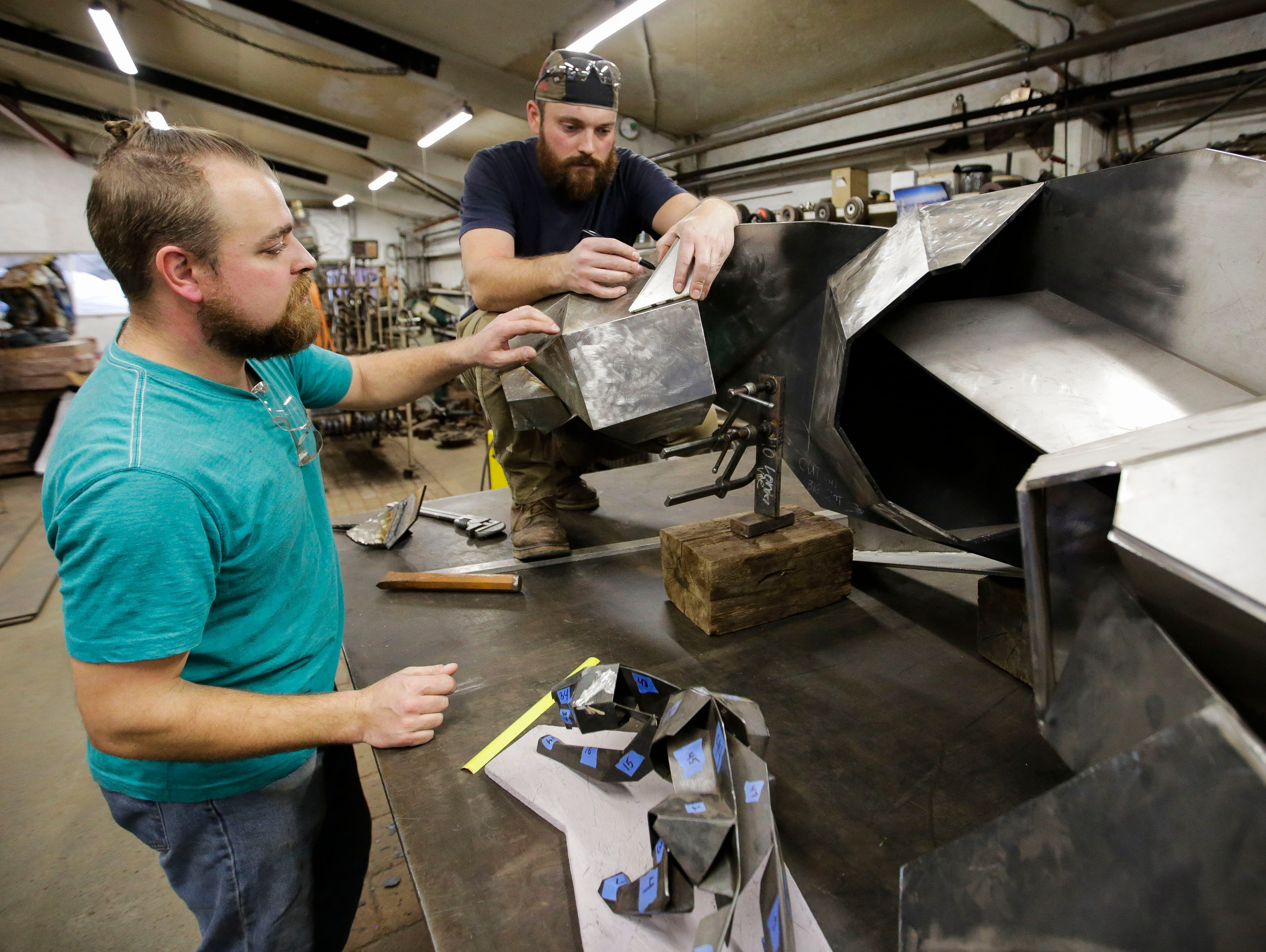 Vincent Kochanowski and August Kochanowski take measurements on their SPASH Panther sculpture on Tuesday, December 25, 2018, at Boleslaw Kochanowski's workshop in Junction City, Wis. The sculpture will be installed at SPASH upon completion.