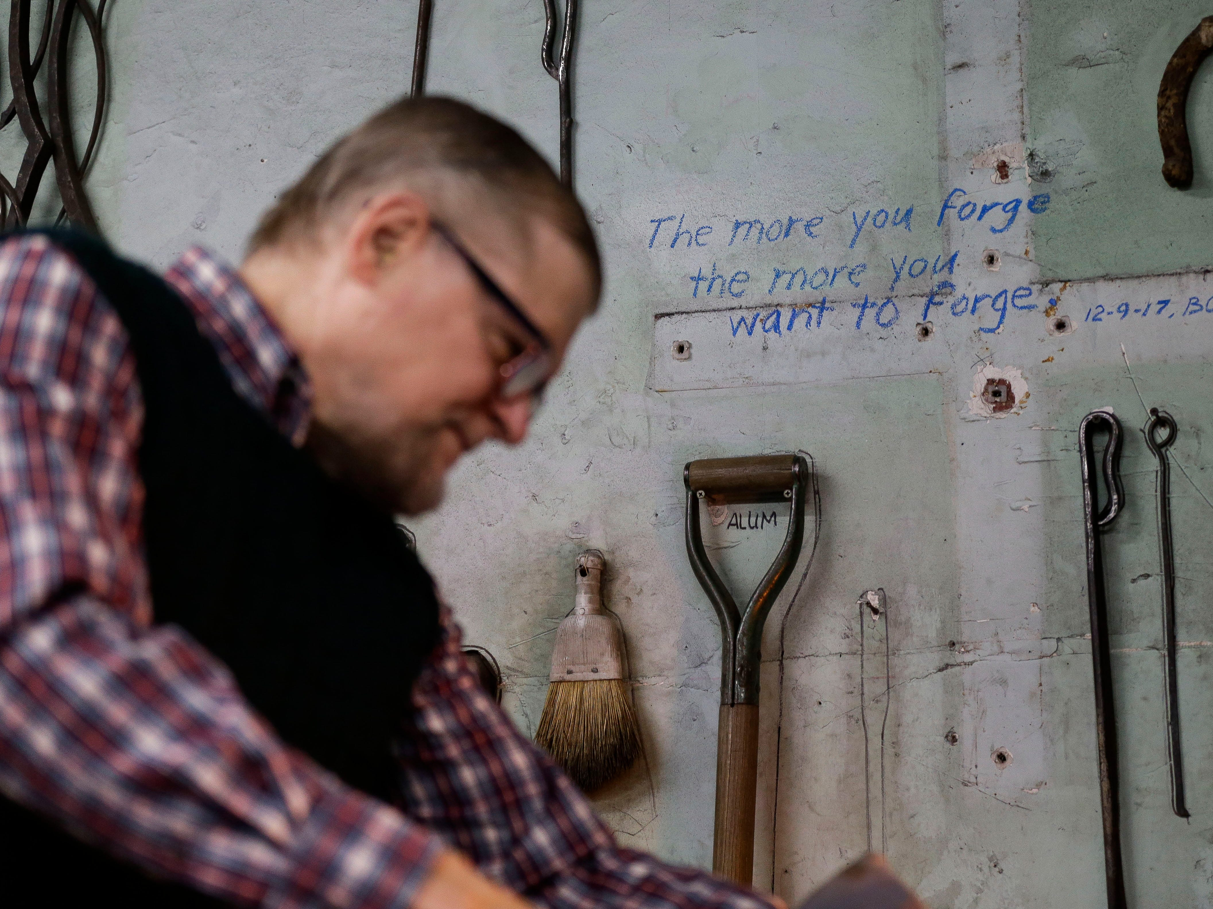 A quote from Boleslaw Kochanowski is shown on the wall as he forges a piece of metal on Tuesday, December 25, 2018, at his workshop in Junction City, Wis. Tork Mason/USA TODAY NETWORK-Wisconsin
