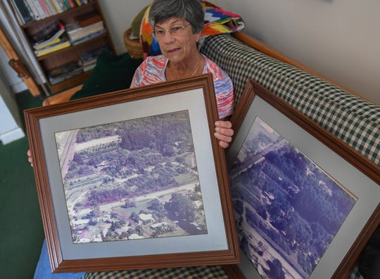 Carol Anne Snyder, co-owner of Lychee Tree Nursery with her husband Harry, holds an aerial photo of their property from 1994, when Kanner Highway, seen on the bottom half of the photo, was only 2-lane traffic. A second photo (right), taken in 2003 shows growth of the number of trees and plants they were  stocking, and Kanner Highway became a 4-lane road with a retention pond between Kanner Highway and their property, seen on the bottom half of that photograph.