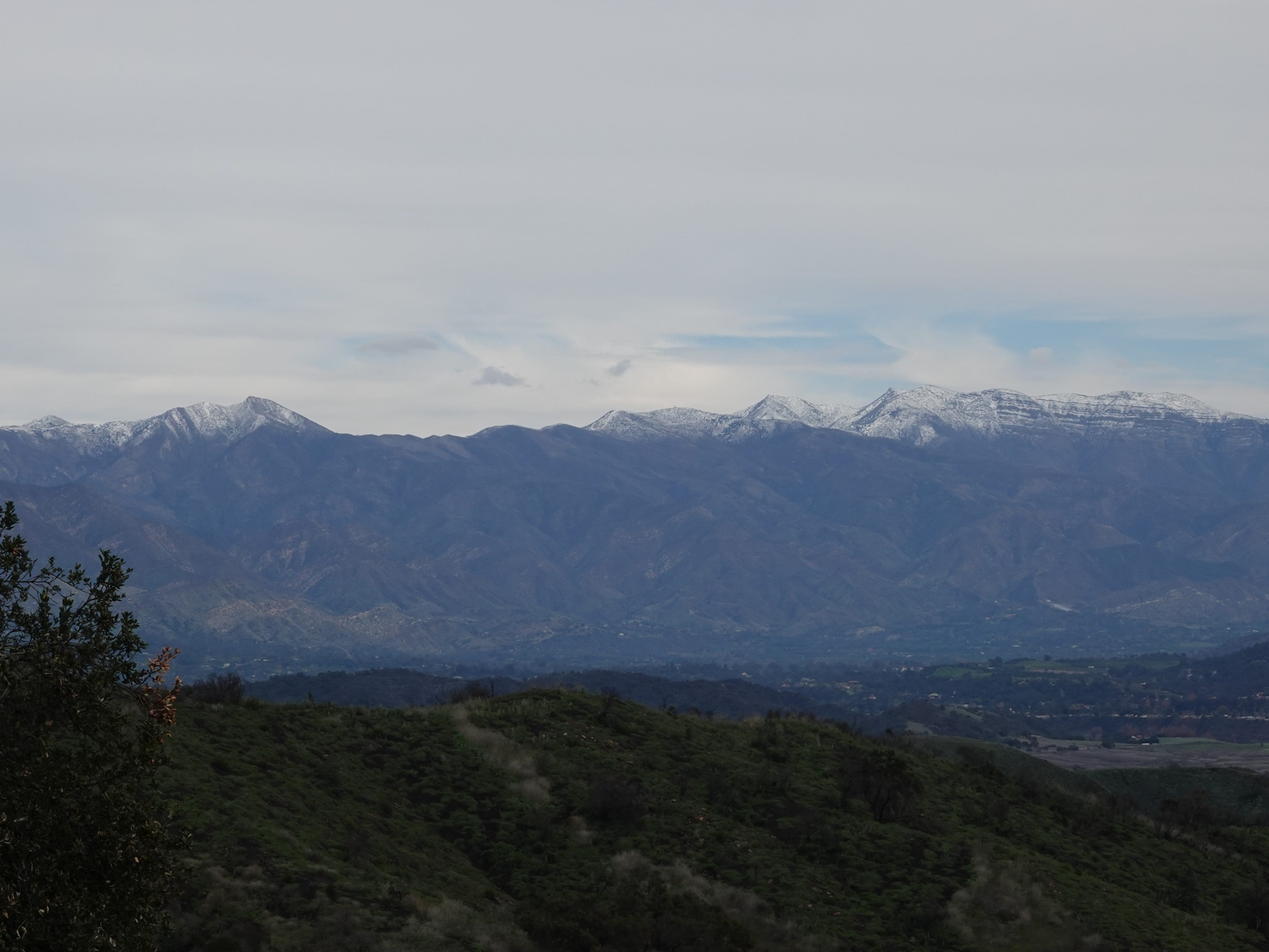 A view of snow-dusted peaks above Ojai Sunday from Highway 150 west of Lake Casitas.