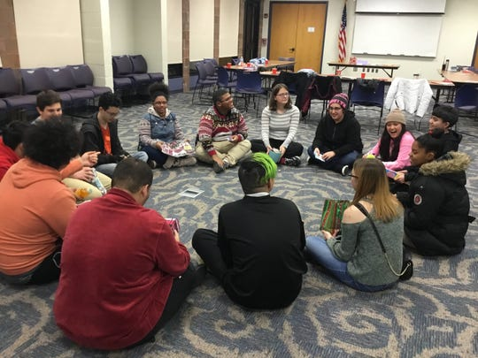 Teens play a Left/Right Story game with presents received during a White Elephant Gift Exchange during Vineland Public Library's Teen Winter Party.