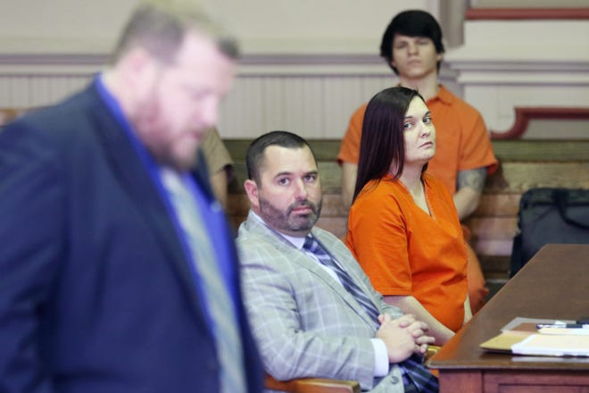 Kelly Dunkle and her attorney Jeremy McClendon listen as Muskingum County Assistant Prosecutor John Litle reads the charges against Dunkle during her sentencing hearing on Monday in Muskingum County Common Pleas Court.