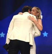 John Krasinski  hugs wife Emily Blunt after winning absolute top sci-fi or horror film Sunday on the Critics' Change Awards.