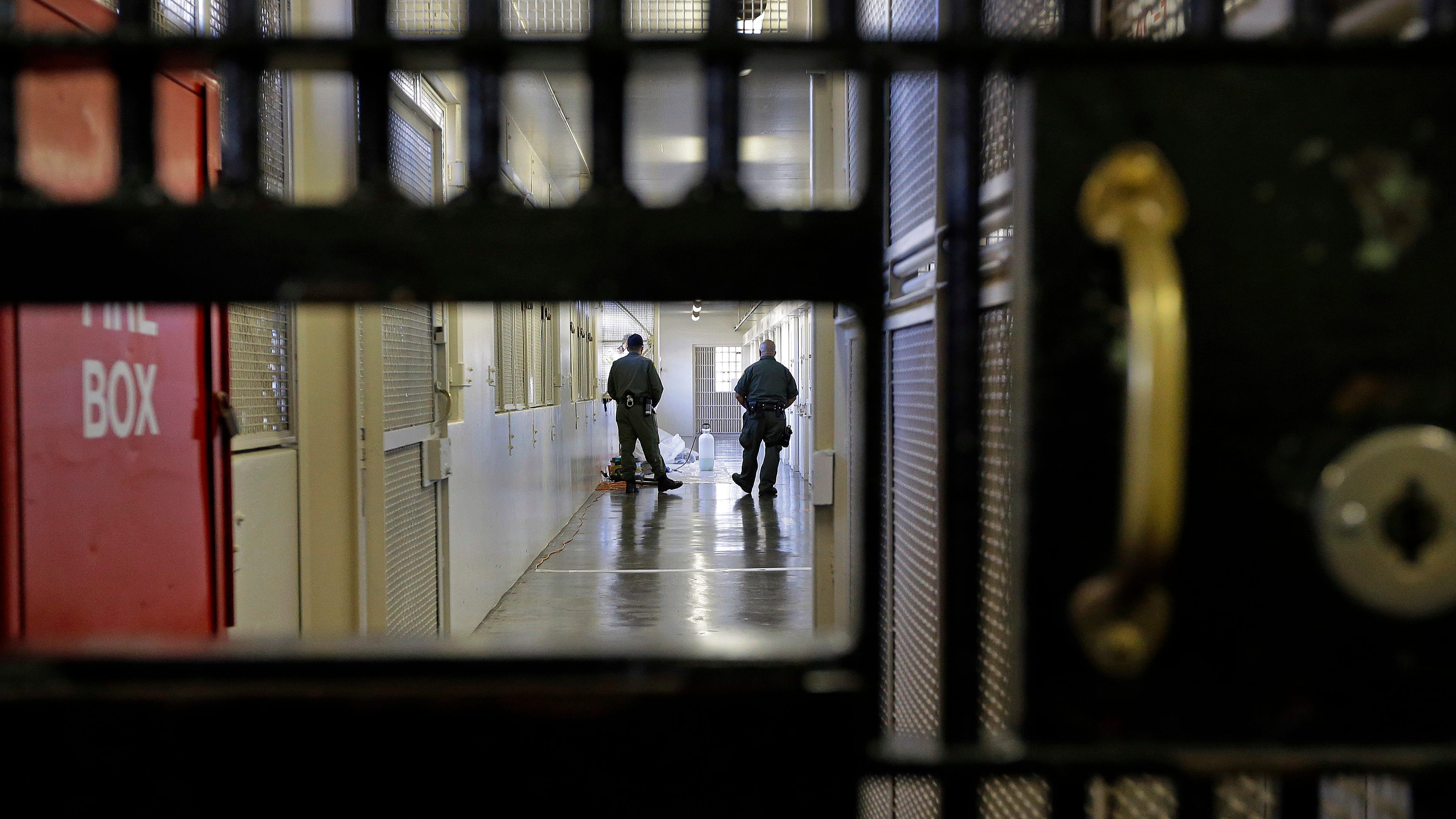 Guards walk a corridor at San Quentin State Prison in San Quentin, Calif.