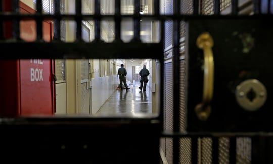Guards walk a corridor at San Quentin State Prison in San Quentin, California.