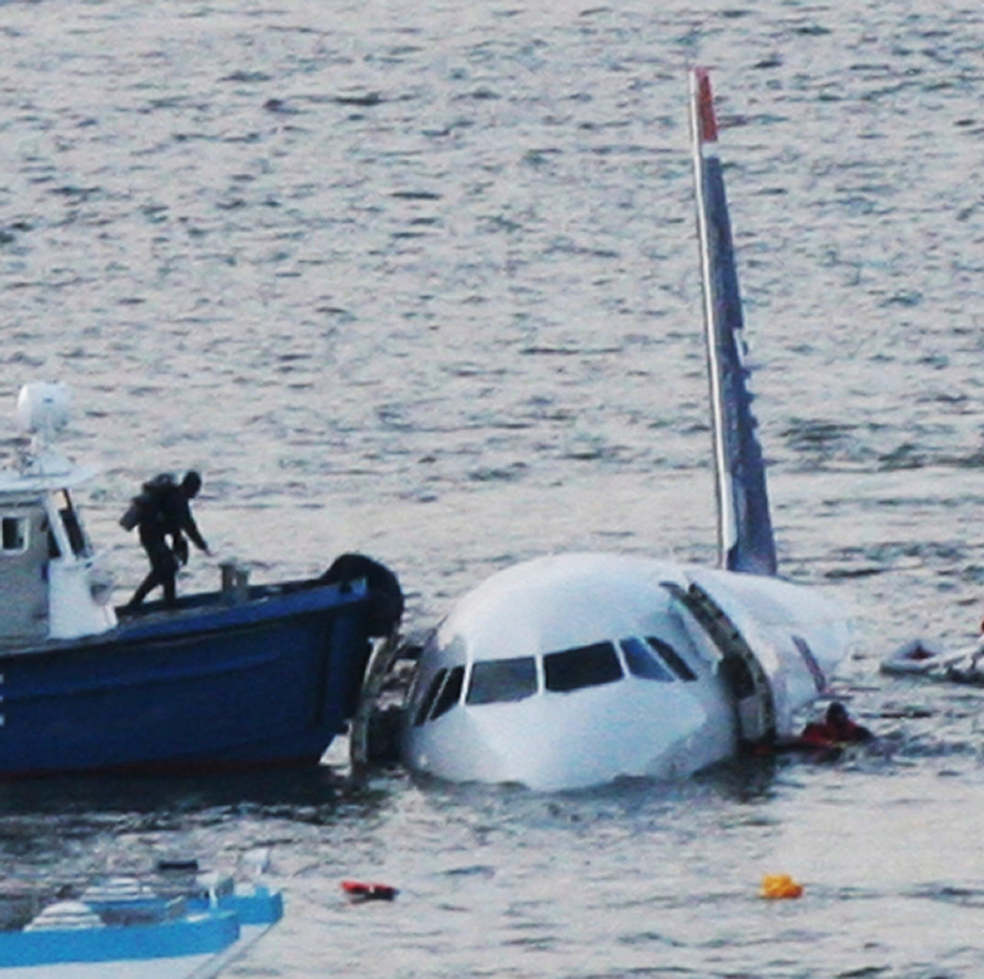 "FILE - In this Jan. 15, 2009 file photo, a diver, left, aboard an NYPD vessel prepares to rescue passengers that escaped from the Airbus 320 US Airways aircraft made an emergency landing in the Hudson River in New York in what came to be known as the ""Miracle on the Hudson"" because everyone survived. It's been 10 years since US Airways flight 1549 landed on the Hudson River after colliding with a flock of geese just after takeoff. (AP Photo/Bebeto Matthews, File) ORG XMIT: NYR101"