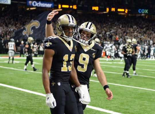 New Orleans Saints wide receiver Michael Thomas (13) reacts with quarterback Drew Brees (9) after catching a pass for a touchdown against the Philadelphia Eagles during the third quarter of a NFC Divisional playoff football game at Mercedes-Benz Superdome.