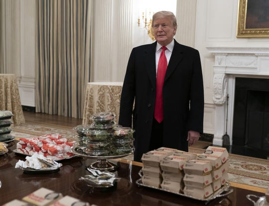 President Donald Trump presents fast food to be served to the Clemson football team at the White House.