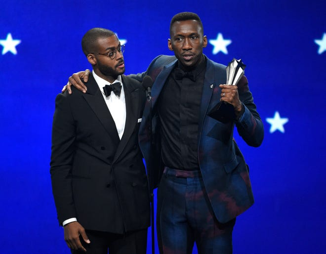 """Mahershala Ali, right, accepts the award for best supporting actor for """"Green Book"""" with the film's composer and pianist Kris Bowers."""