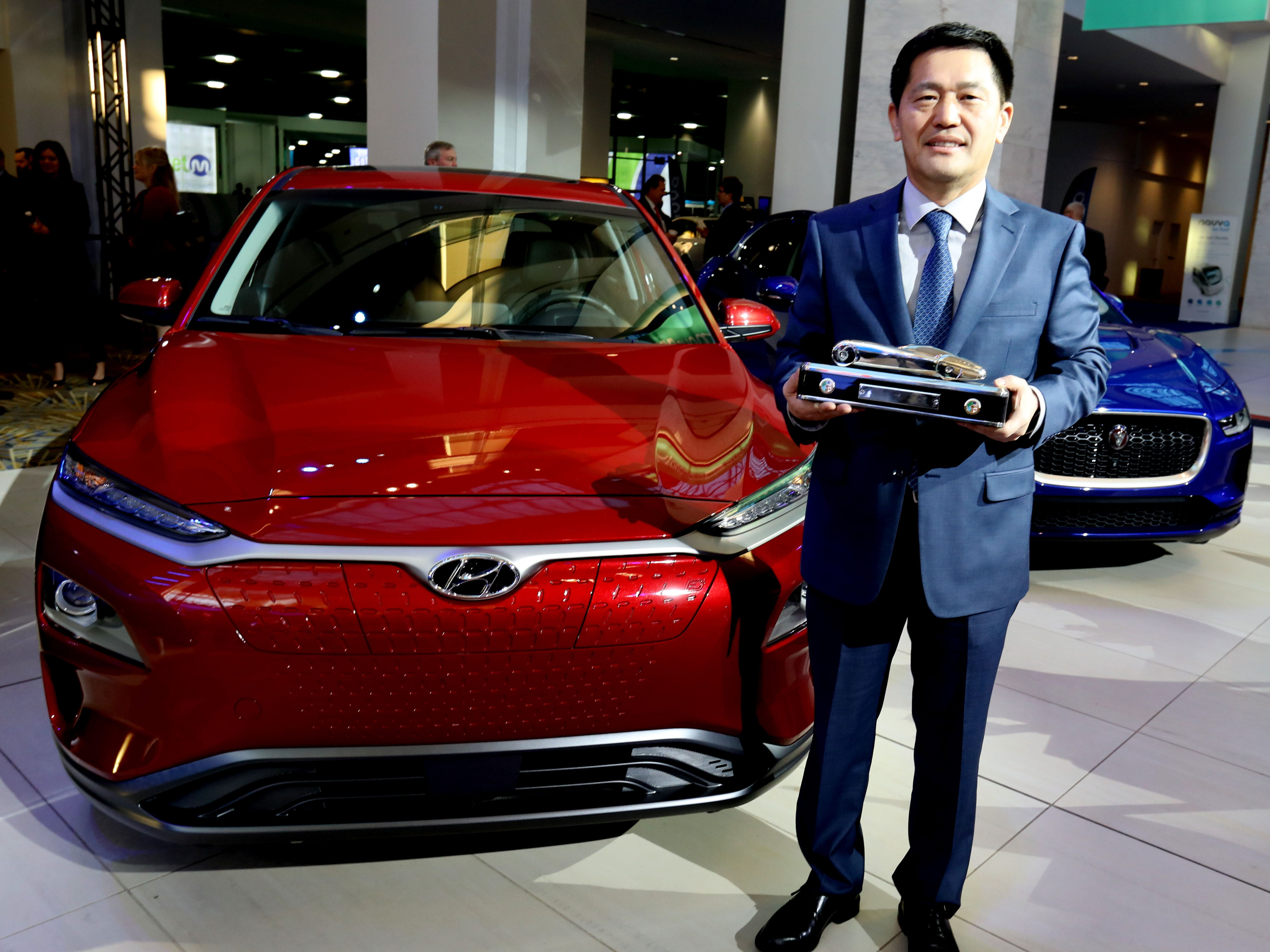 William Lee, president and CEO of Hyundai Motor North America holds the trophy in front of the Hyundai Kona which won the North American Sport Utility of the Year.