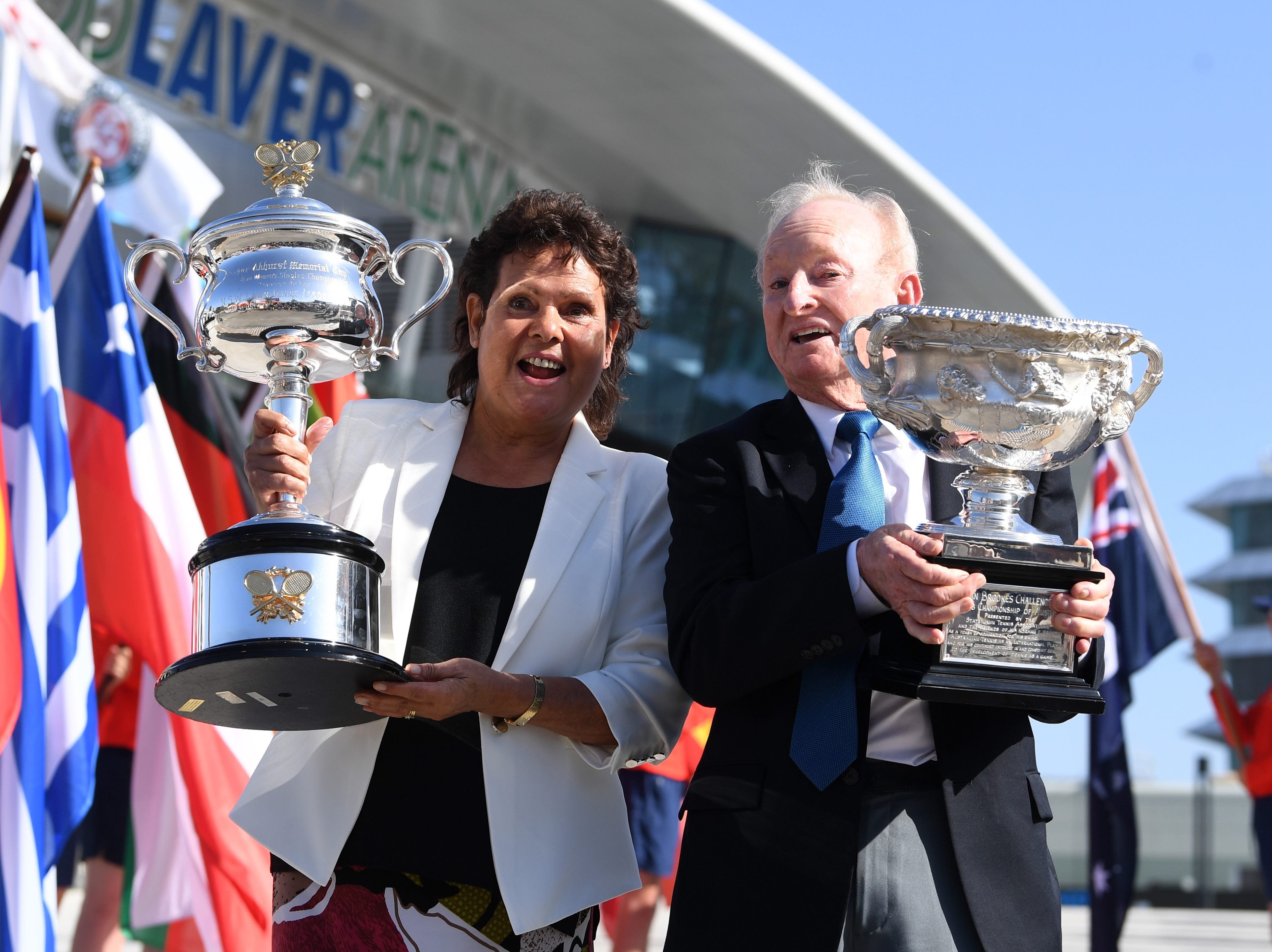 Australian tennis legends Evonne Goolagong Cawley, left, and Rod Laver bring the Daphne Akhurst Memorial Cup (given to the women's singles champion) and the Norman Brookes Challenge Cup (given to the men's singles champion) to Melbourne Park.