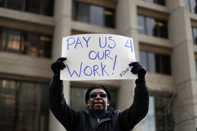 Christopher Belcher, a Department of Veterans Affairs employee, holds a sign during a rally to call for an end to the partial government shutdown, in Detroit, Thursday, Jan. 10, 2019. (AP Photo/Paul Sancya) ORG XMIT: MIPS105