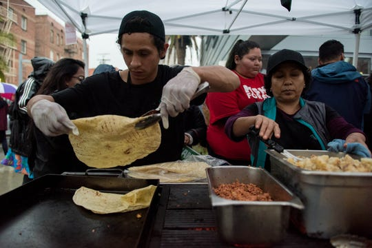 Zingo tacos prepare breakfast burritos outside of Robert F. Kennedy Community Schools in Los Angeles, California, on Monday.