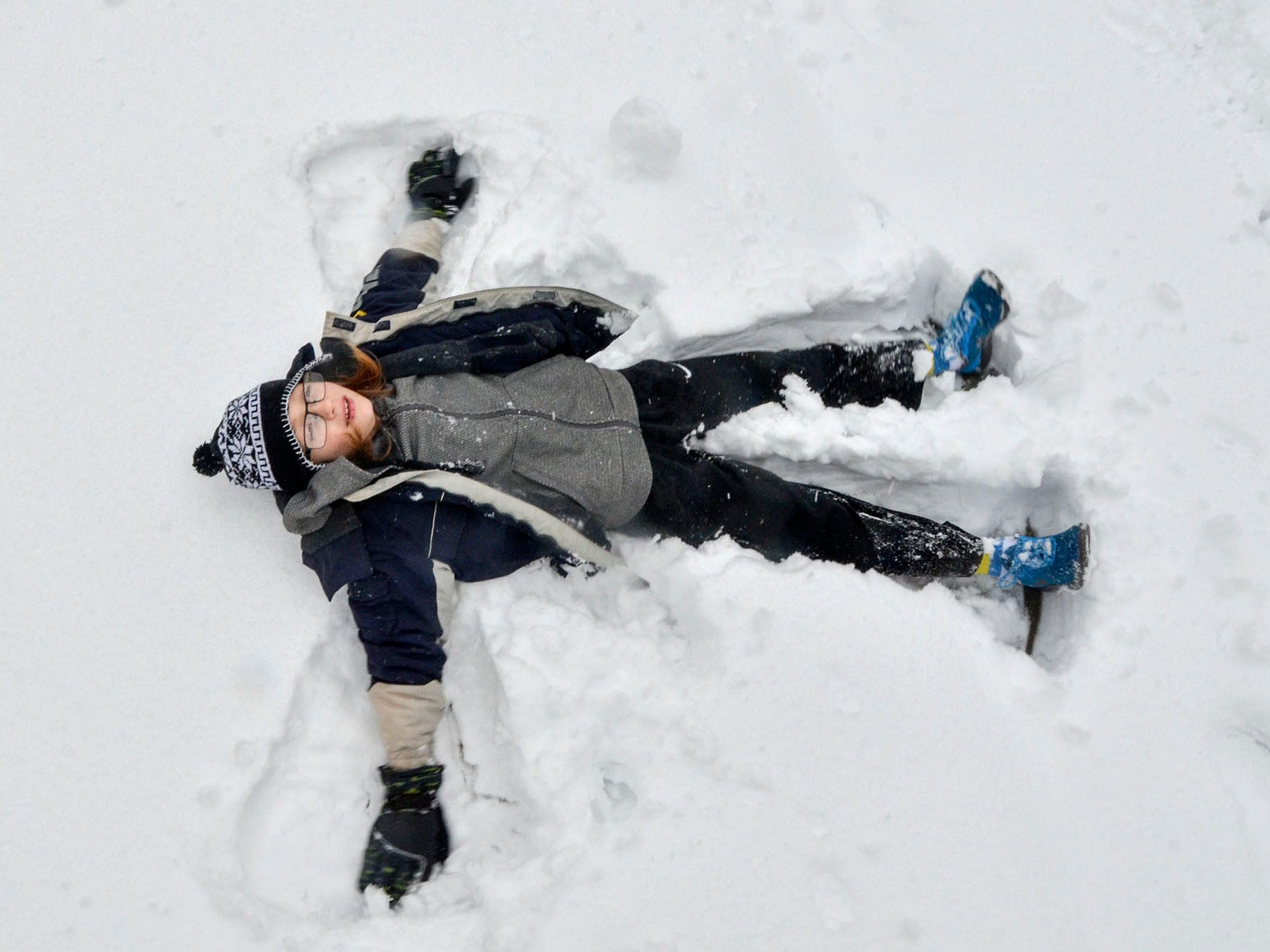 Noah Shober makes a snow angel outside of his house in Terre Haute, Ind., on Saturday, Jan. 12, 2019. A massive winter snowstorm making its way across the Midwest and into the Mid-Atlantic region blanketed most of Missouri and several other states. The storm moved east into Missouri, Iowa, Illinois and Indiana, covering roads and making driving dangerous. (Austen Leake/The Tribune-Star via AP) ORG XMIT: INTET102