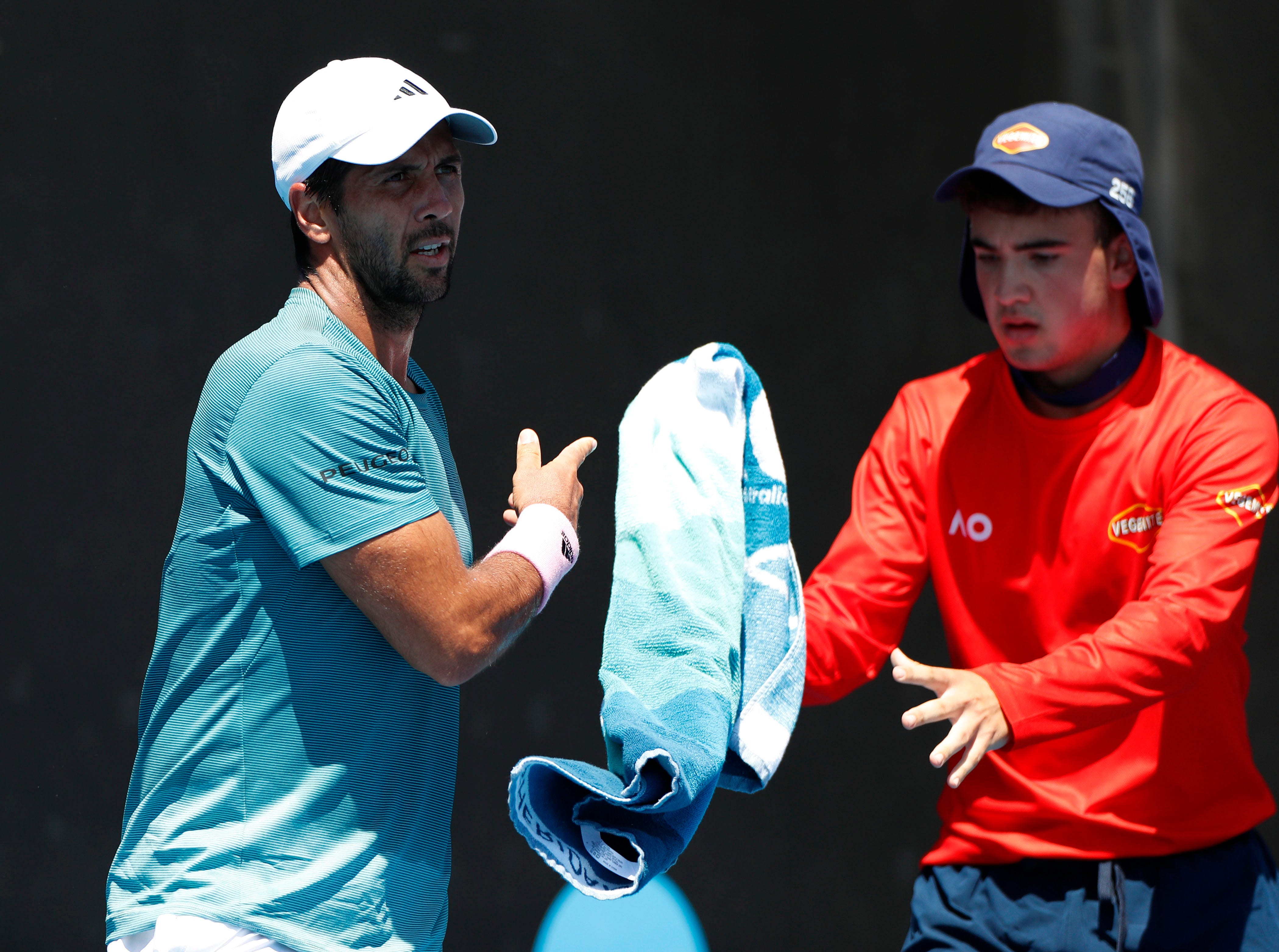 Spain's Fernando Verdasco, the No. 26 seed, throws a towel to a ball boy during his first-round victory over Miomir Kecmanovic of Serbia.