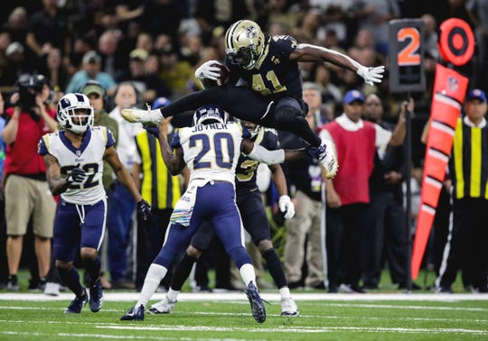 New Orleans Saints running back Alvin Kamara (41) hurdles over Los Angeles Rams free safety Lamarcus Joyner (20) during the fourth quarter at the Mercedes-Benz Superdome.