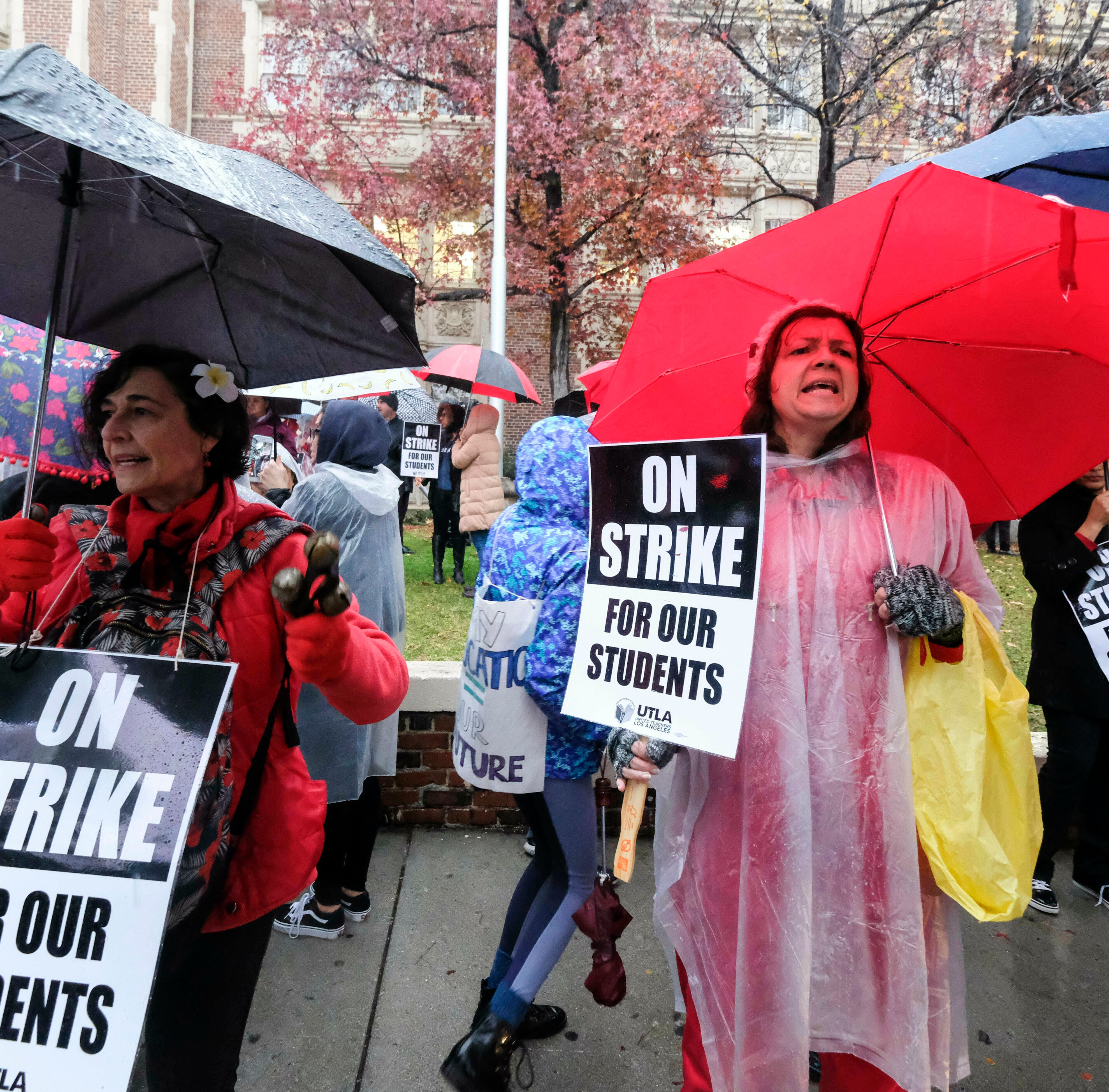 Teachers strike in the rain outside John Marshall High School, Monday, Jan. 14, 2019, in Los Angeles. Tens of thousands of Los Angeles teachers are striking after contentious contract negotiations failed in the nation's second-largest school district.(AP Photo/Ringo H.W. Chiu) ORG XMIT: CARC107