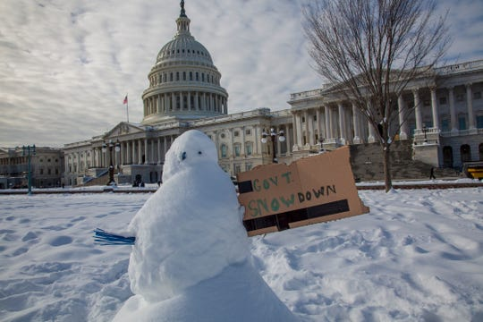 A snowman with a message about the government shutdown is pictured outside Capitol Hill
