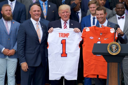 President Donald Trump (center) holds up a Clemson football jersey along with school president James P. Clements (left) and head coach Dabo Swinney (right) during the team's 2017 White House visit.