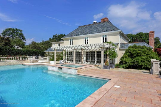 The backyard oasis features inground marble pool and a cabana house.