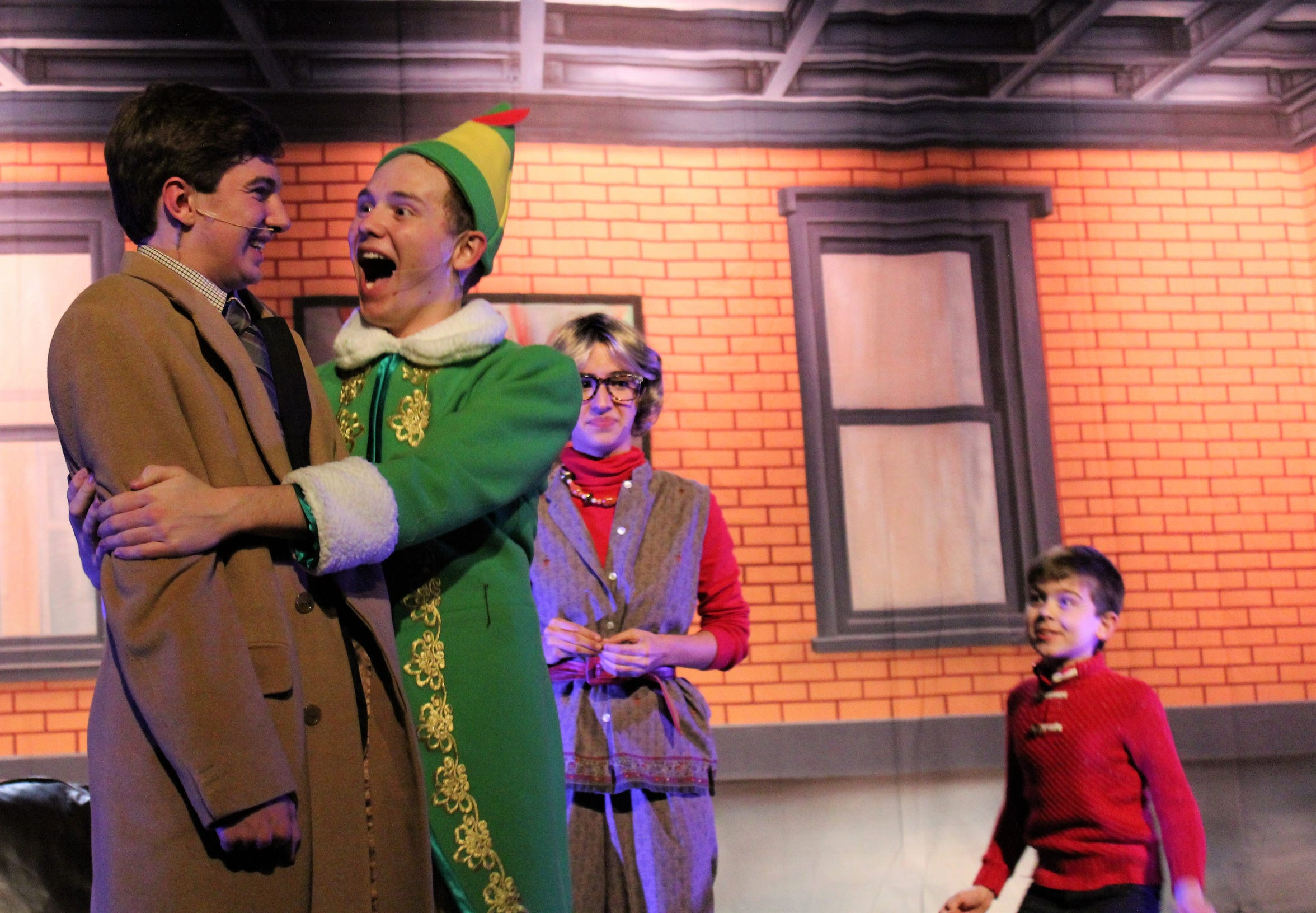 "Buddy hugs his dad, Walter Hobbs (Trevor Cox, left) as his new mom (Mary Moore) and brother (Phoenix Lowe) look on in this rehearsal scene from ""Elf, the Musical, Jr."""