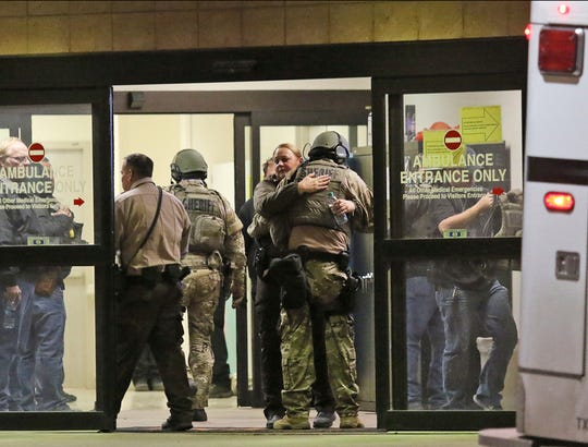 Ector County Sheriff deputies hug in the ambulance entrance at Medical Center Hospital after three sheriff's deputies were shot in the line of duty, according to the Odessa American, late Monday, Jan. 14, 2019, in North Odessa, Texas. (Jacob Ford/Odessa American via AP)