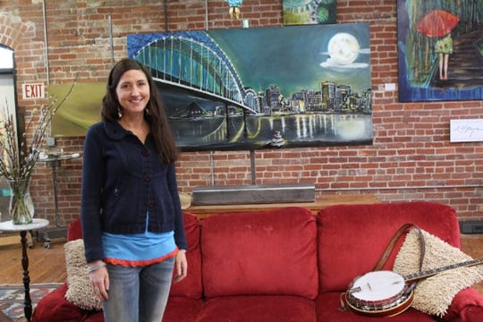 "North Carolina artist Nancy Hilliard Joyce stands in front of her painting ""Moon Over Memphis"" in 2014. The artwork was commissioned by Balsam Range for an album cover."