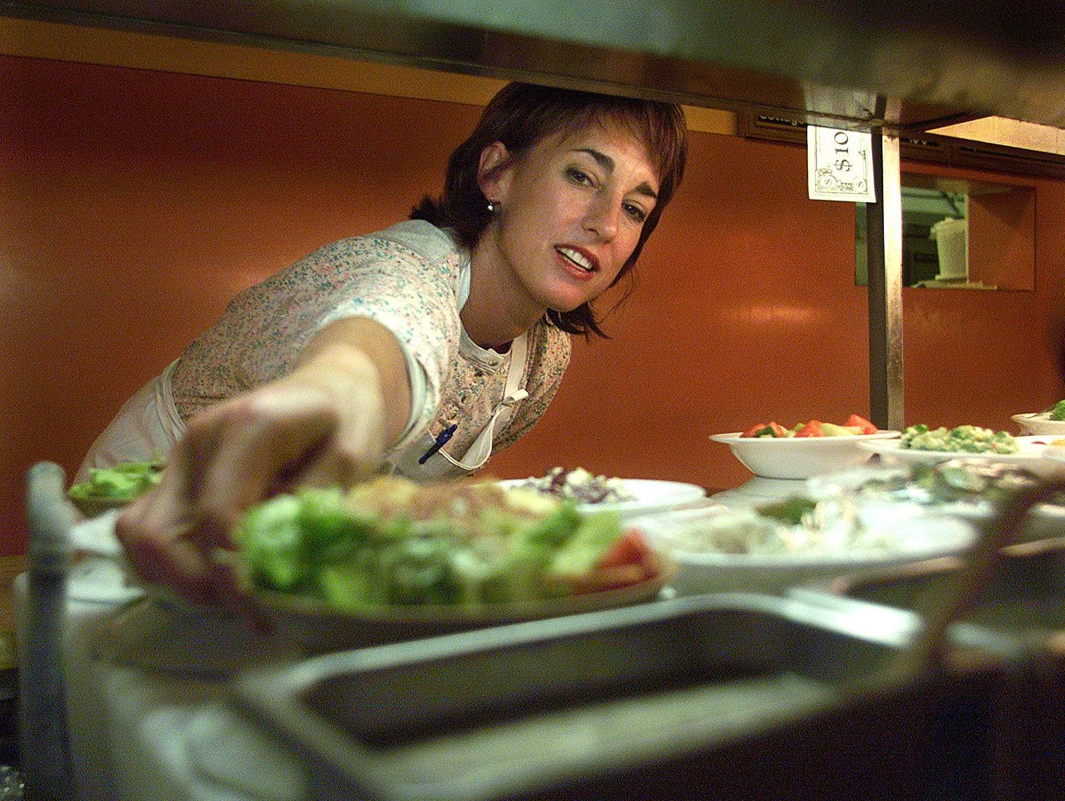 Rita DeVore, owner of Shranks Cafeteria & Catering Co., arranges salads this week in her restaurant in 1999.