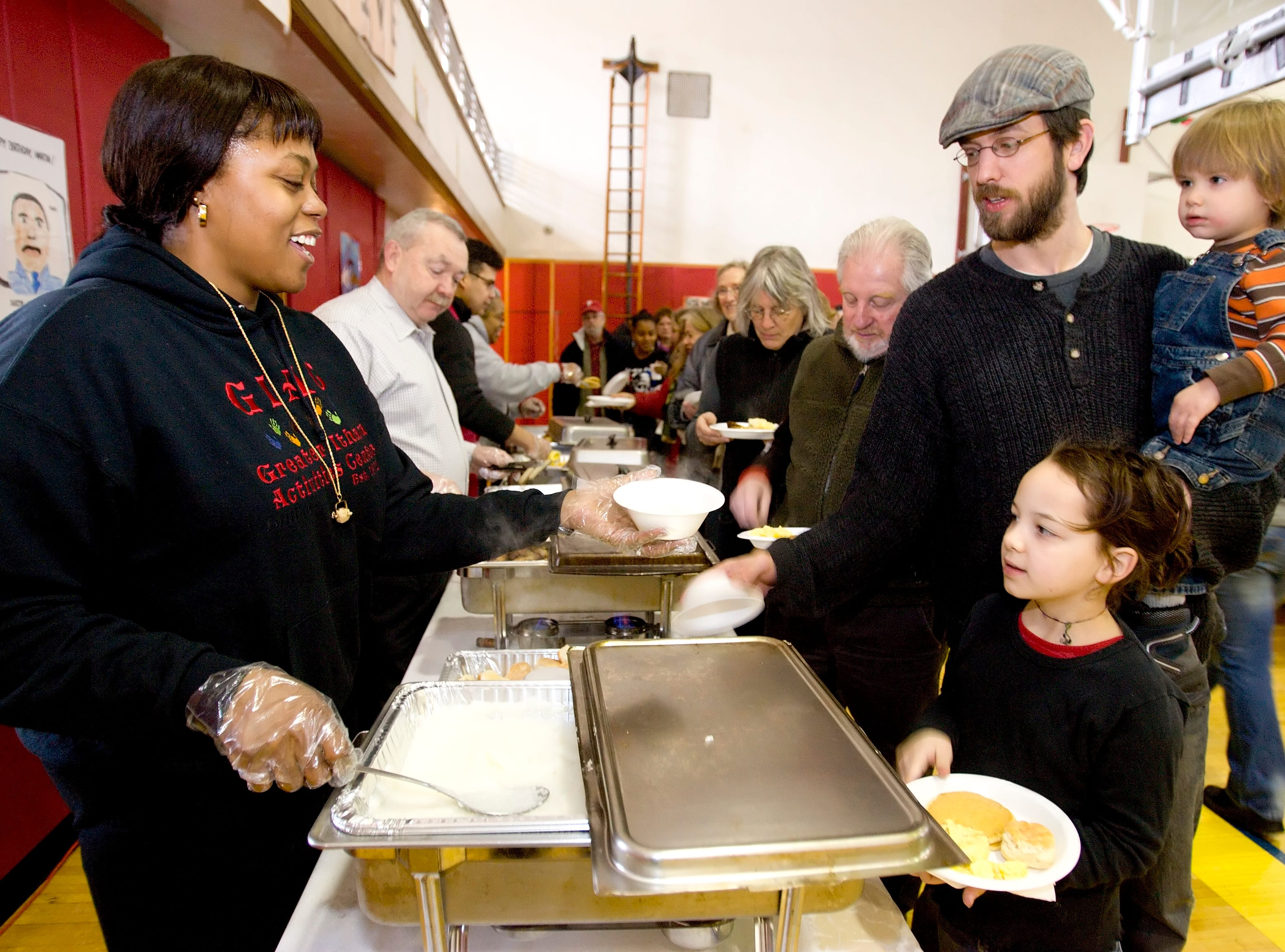 2009: Rasheedah Boyd, left, serves grits to Mark Thornton and his two children Samuel, left, and Alyssa Thornton on Saturday at the Greater Ithaca Activites Center's Annual Martin Luther King Jr. Breakfast.