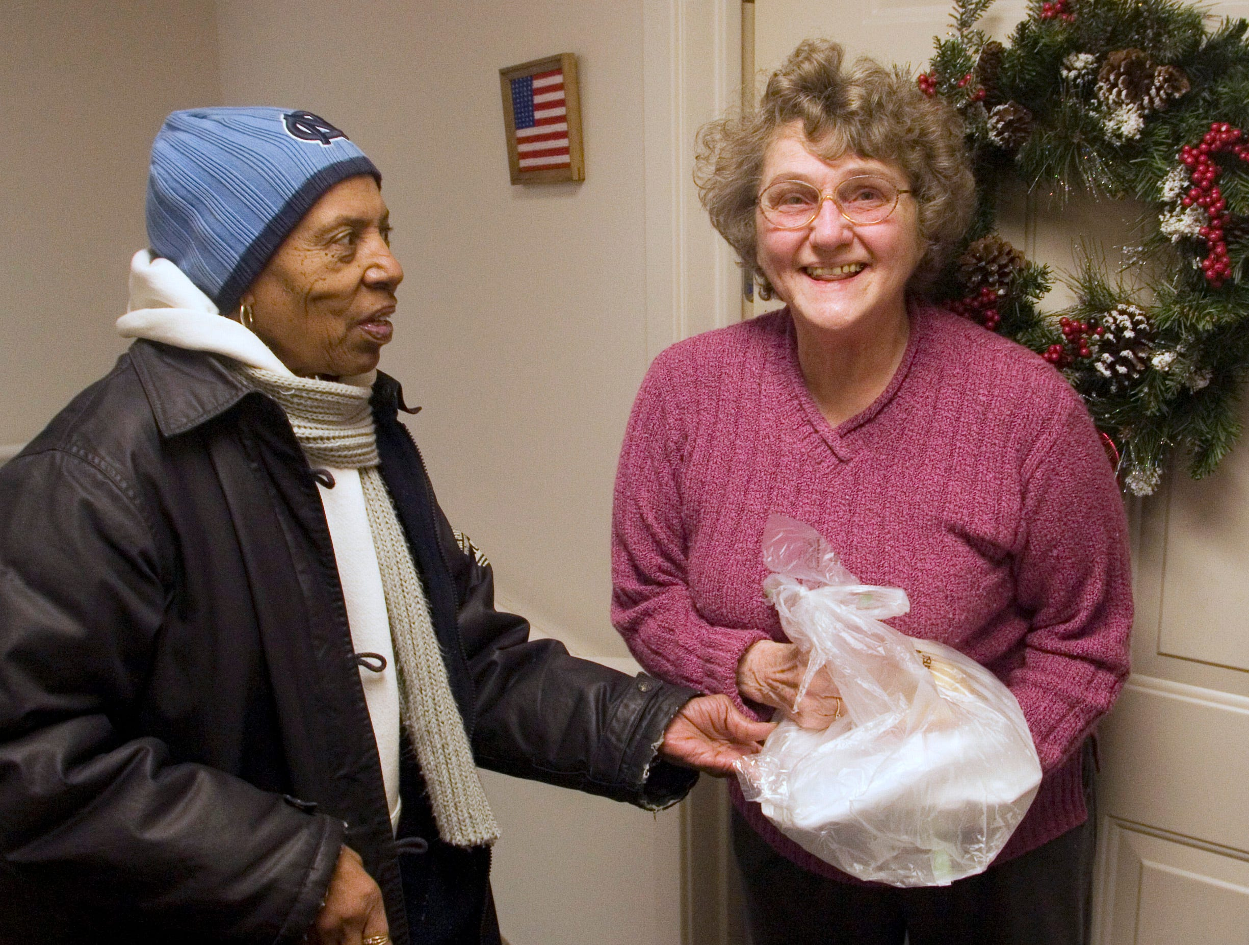 2008: Brenda Nash, a member of  Queen City Temple 146, delivers a meal to Clemens Manor resident Doris Sortland on Martin Luther King Jr. Day Monday. .