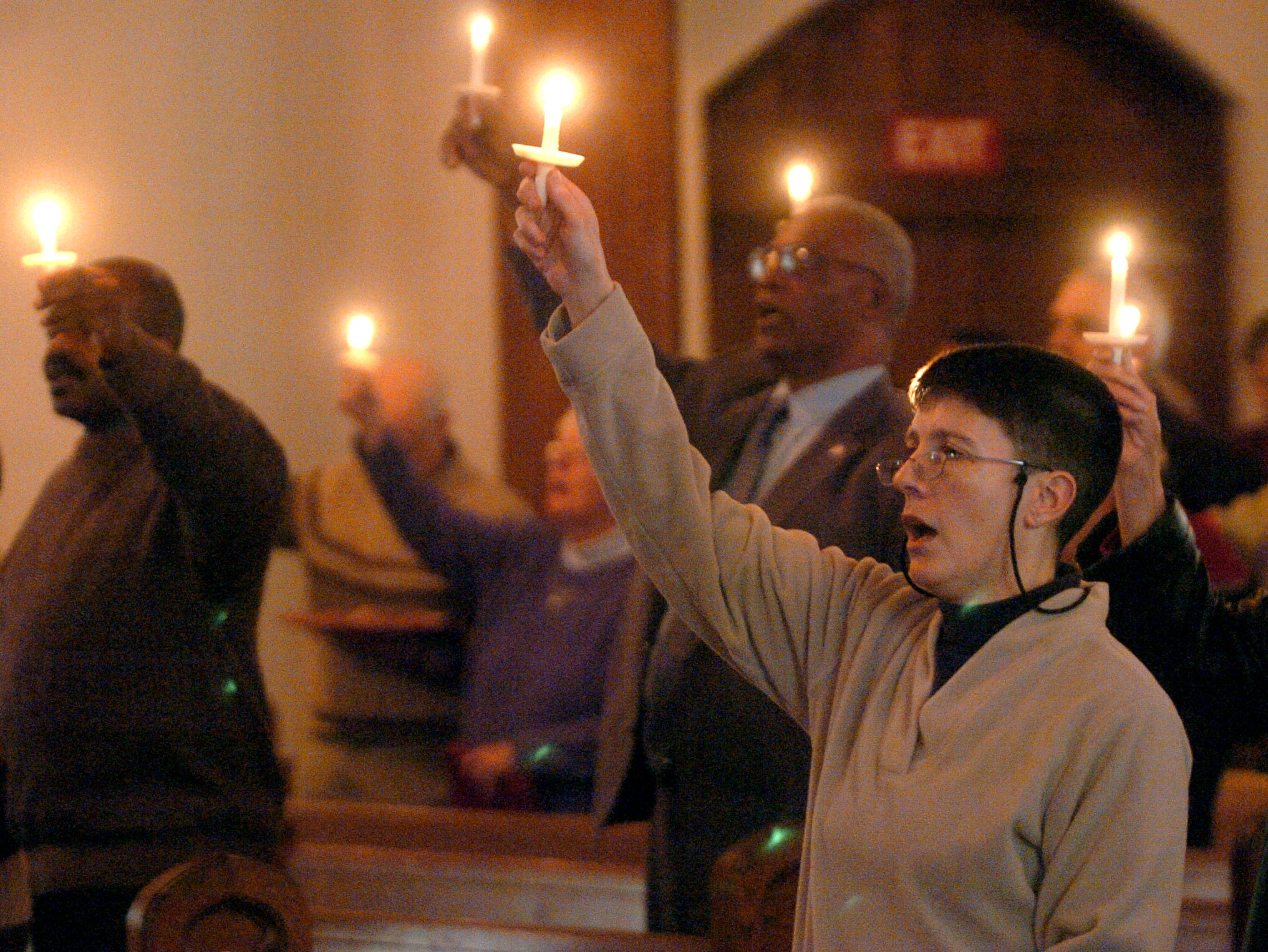 2006: Pat Pomeroy, right, of Endicott and other churchgoers raise candles while singing 'We Shall Overcome' during a church service in celebration of Dr. Martin Luther King Jr., at Central United Methodist Church Sunday in Endicott.