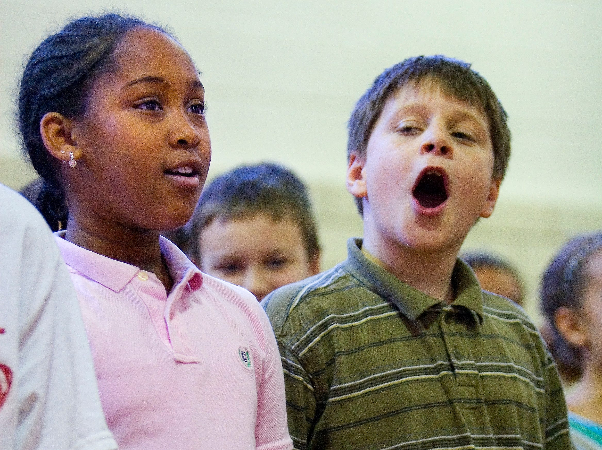 2009: Fassett Elementary School students Aaliyan Coleman, Robert Vischansky and Matt Burge sing a song honoring Martin Luther King Jr. during a school assembly Friday afternoon.