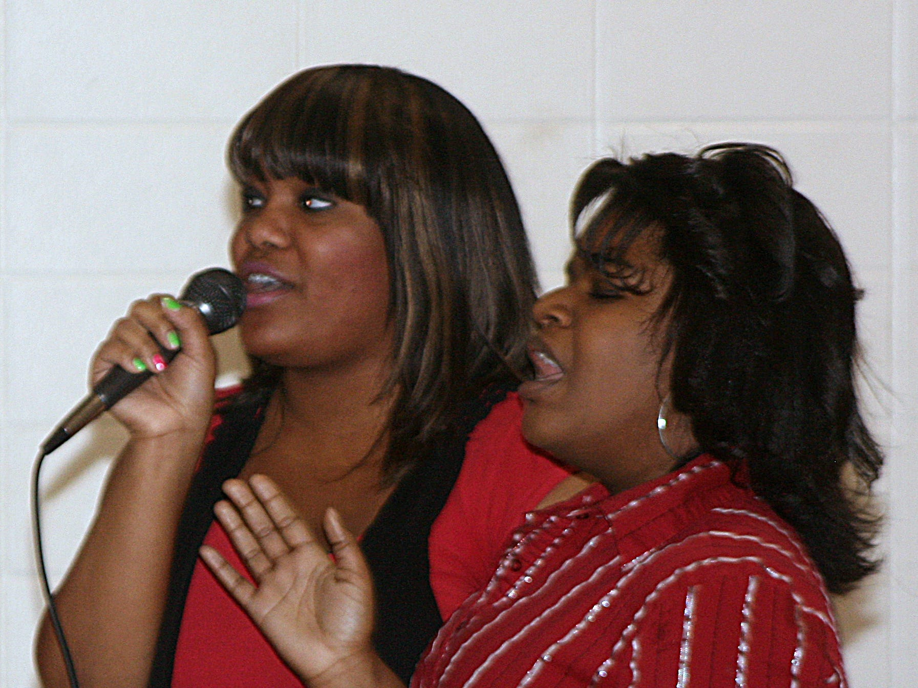 2012: Eboni Martin, left, and Anissa Scarborough, of the Faith Temple Community Church of God and Christ's Youth on Fire Choir, sing Monday during the 14th annual Together We Dine event held at the Ernie Davis Community Center in Elmira to celebrate Dr. Martin Luther King Jr. Day.