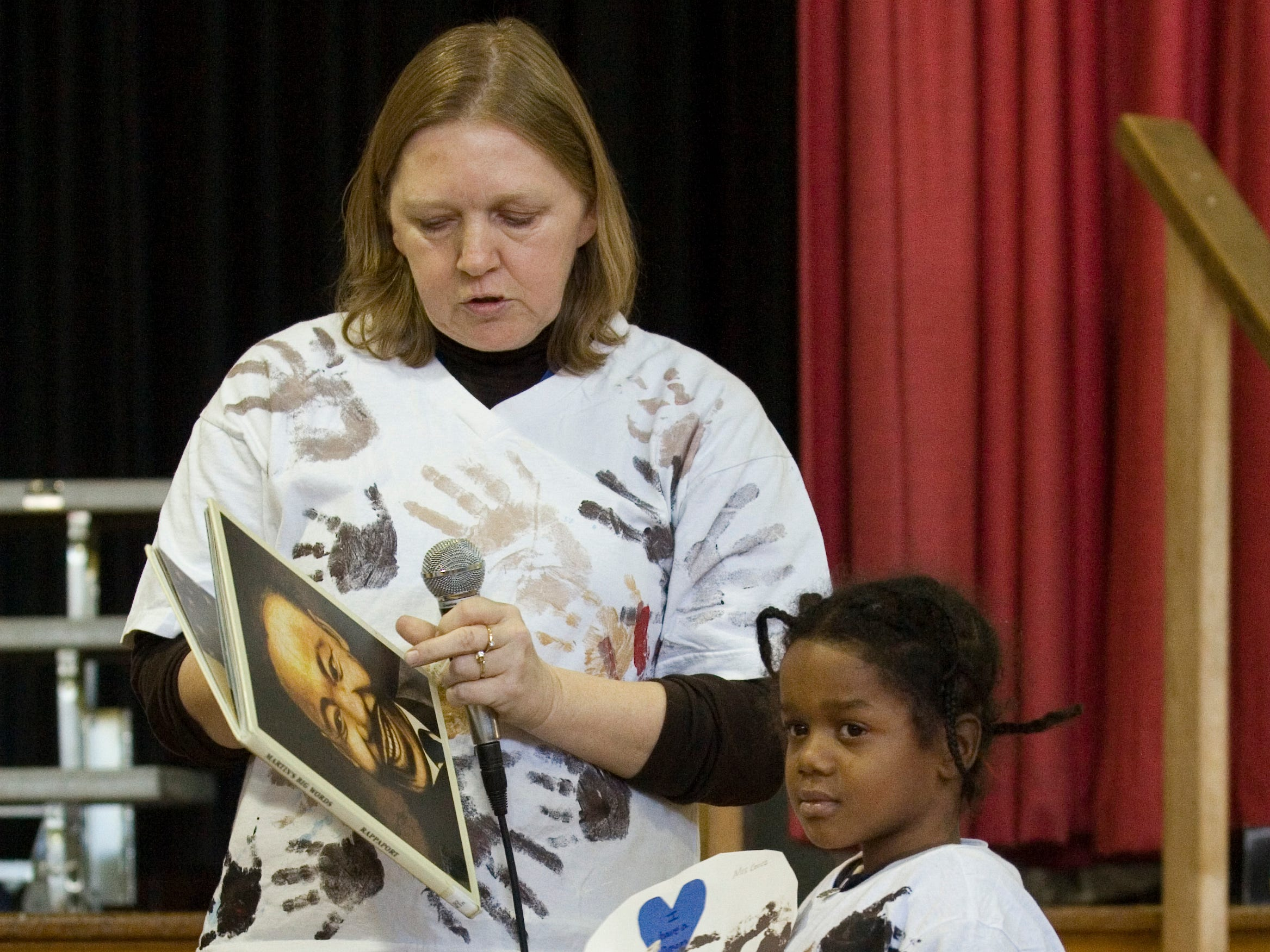 2009: Fassett Elementary School teacher Christina Cecce tals about the projects her students did in recognition of  Martin Luther King Jr. as pre-kindergarten student Jas'zon Campbell displays a drawing with different colored hand prints on it.