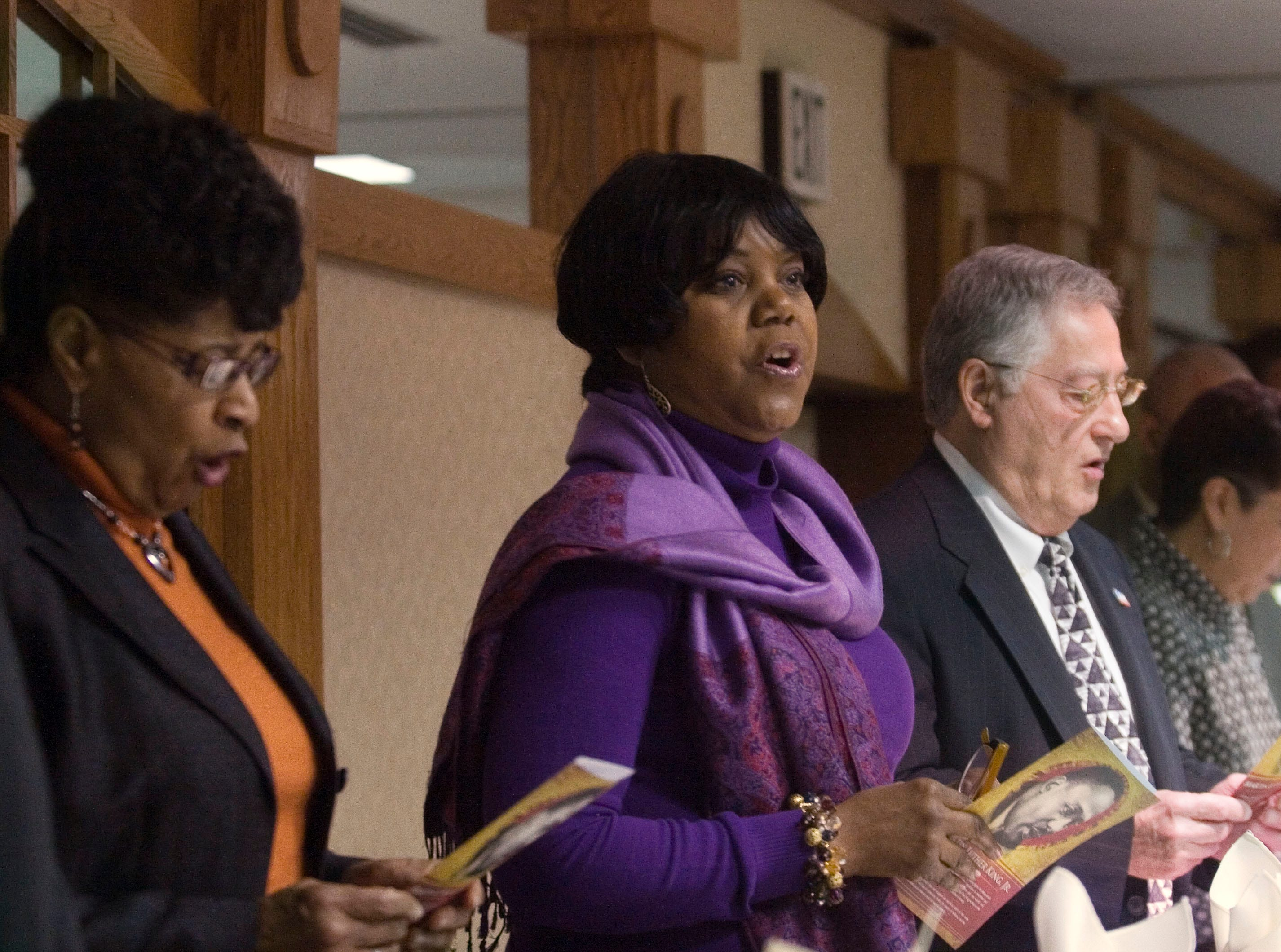 """2010: Martin Luther King Jr. breakfast participants, from left, Georgia Verdier, president of the Elmira-Corning NAACP, Holly Strickland, Ernie Davis Middle School assistant principal and Richard Negri, Corning mayor, join in the singing of  """"Lift Every Voice and Sing""""  before breakfast is served at Radisson Hotel in Corning Saturday morning."""