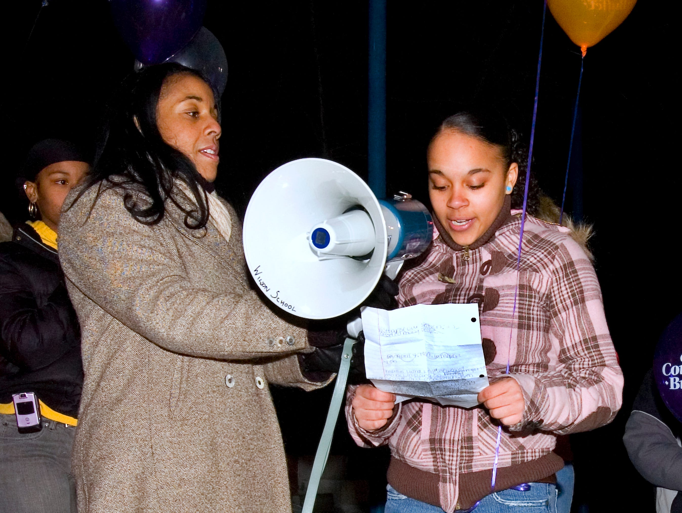 2008: Ana Shaello-Johnson, left, director of Binghamton City Youth Bureau, stands with Ciara Mondulfi, 15, of Binghamton while she makes a speech to remember Martin Luther King at the MLK Promenade on Wall Street in Binghamton on Monday evening.